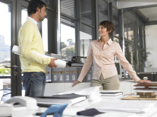 Businesswoman and man in office talking, man holding plans