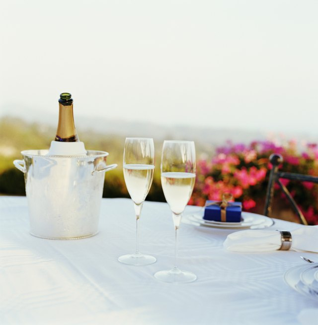 Two glasses of champagne on table, bottle in ice bucket in background