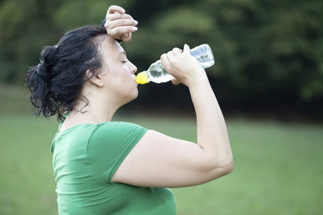 Sweaty overweight woman drinking water after a long run
