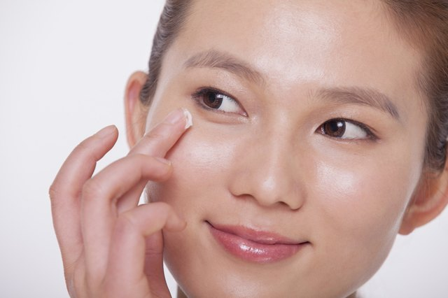 Close up on the face of a smiling young woman applying cream to her face, studio shot