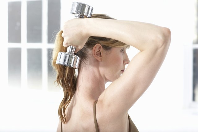 Woman holding dumb-bell behind head, side view