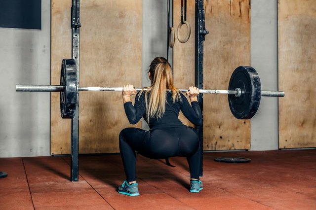 Back view fit attractive girl working out legs or squat with heavy barbell in fitness center.Young woman doing a cross-training in gym.