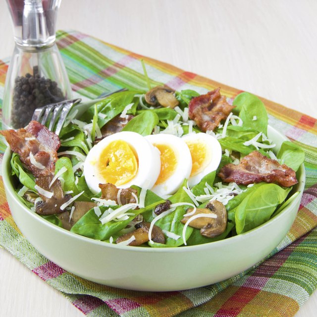Tasty salad with spinach, bacon, champignon mushrooms, cheese, egg
