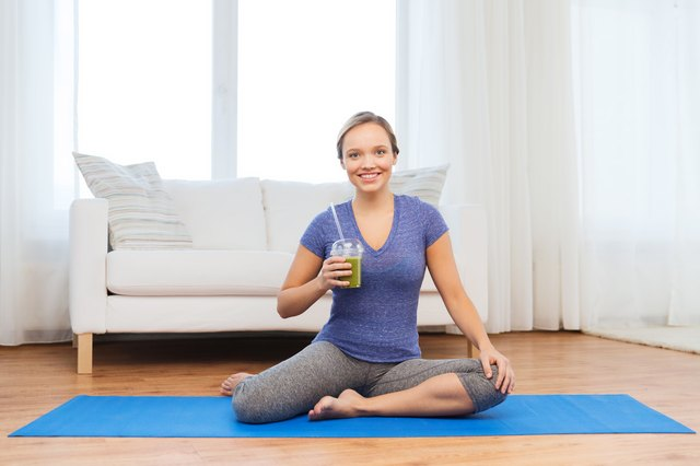 happy woman with smoothie sitting on mat at home