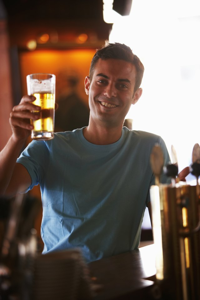 Young man holding up glass of beer in bar, smiling, portrait
