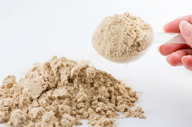 The hand raise a spoon measure Whey protein.