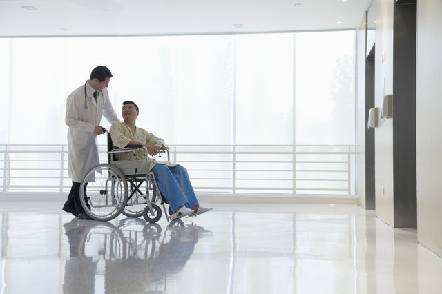 Doctor pushing and assisting patient in the hospital, Beijing, China