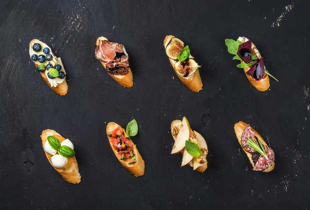 Italian crostini with various toppings on black plywood background