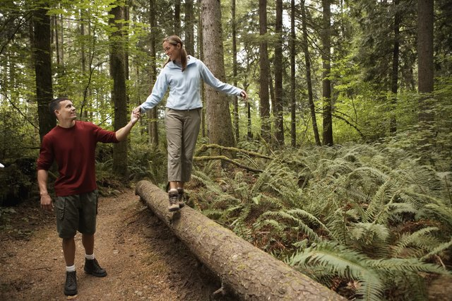 Man holding woman's hand as she walks across log in forest