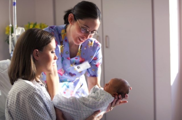 a caucasian mother shows off her newborn baby to a nurse while recovering in a hospital bed