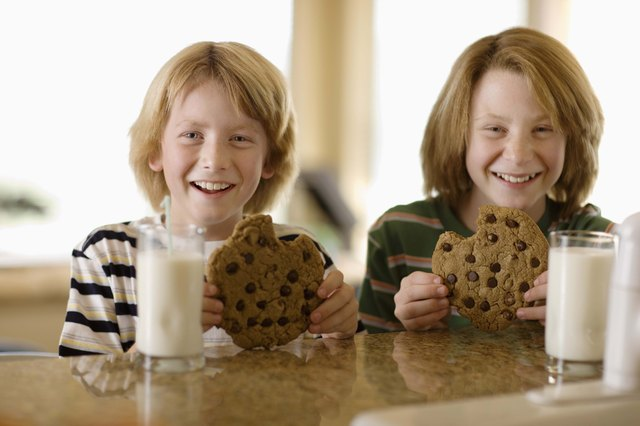 Boys having milk and cookies at table