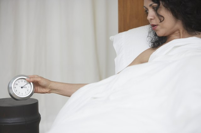 Woman looking at alarm clock from bed