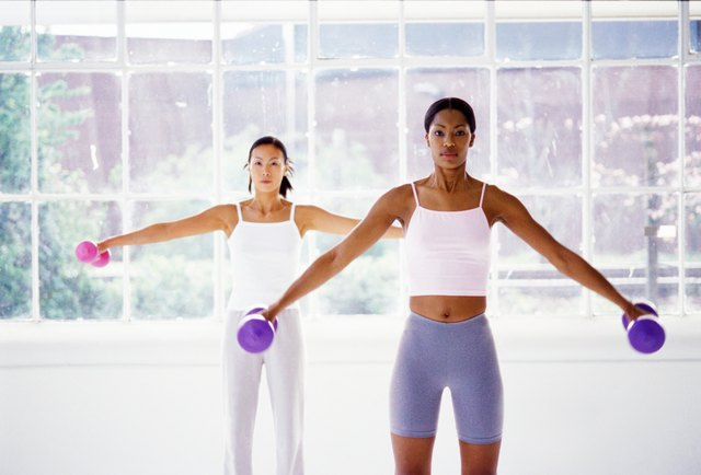 two young woman exercising with dumbbells