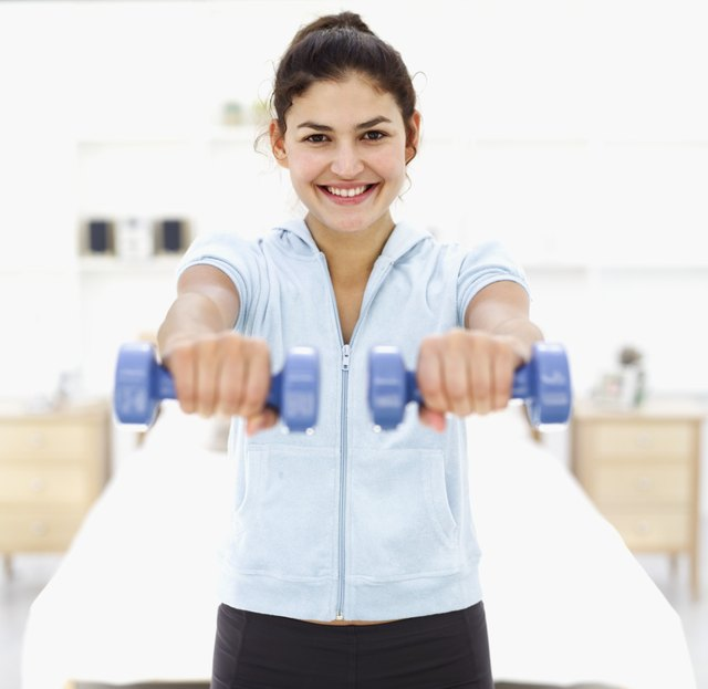Portrait of a young woman smiling exercising with dumbbells