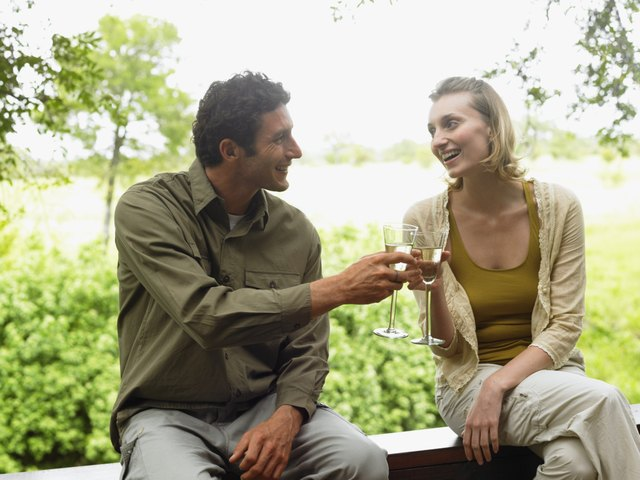 Couple sitting on balcony toasting each other with drinks, smiling