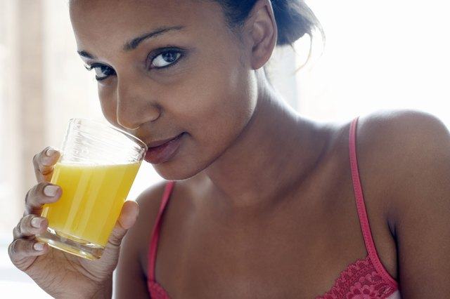 Young woman drinking glass of juice, close-up, portrait