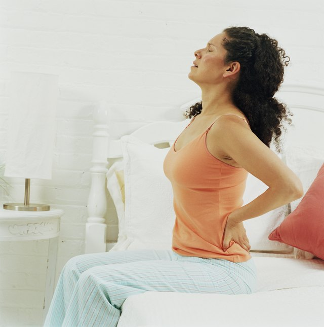 Woman sitting upright on bed holding back, eyes closed