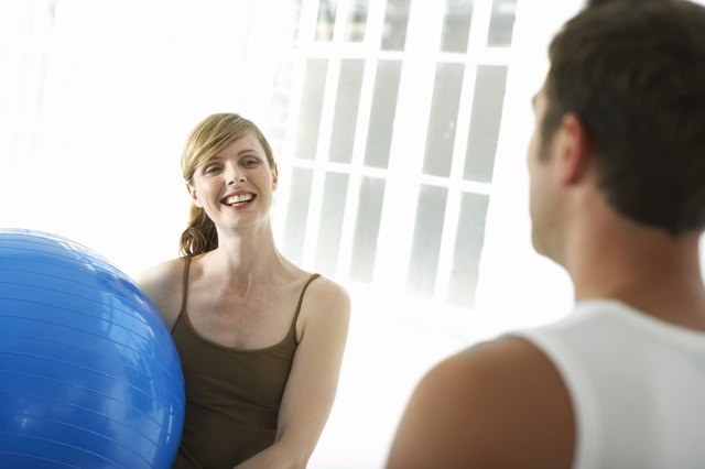 Woman holding exercise ball, smiling at man
