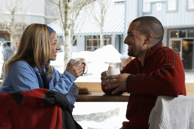 Man and woman with coffee cups smiling at one another in cafe