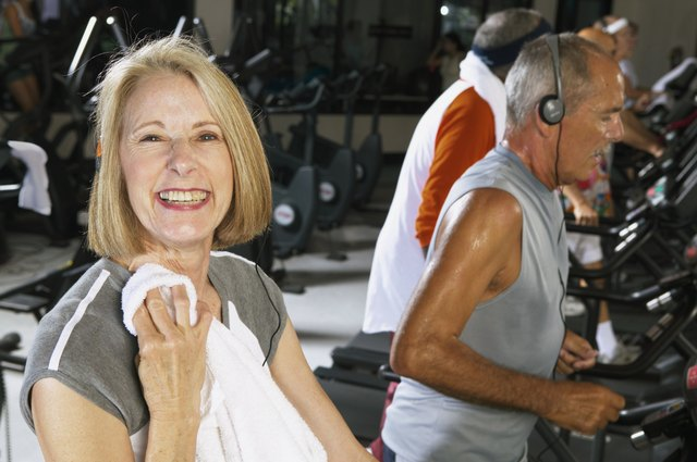 Senior woman in gym holding towel, smiling, portrait