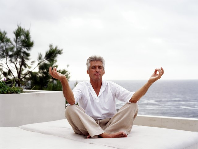 Mature man meditating by ocean, eyes closed