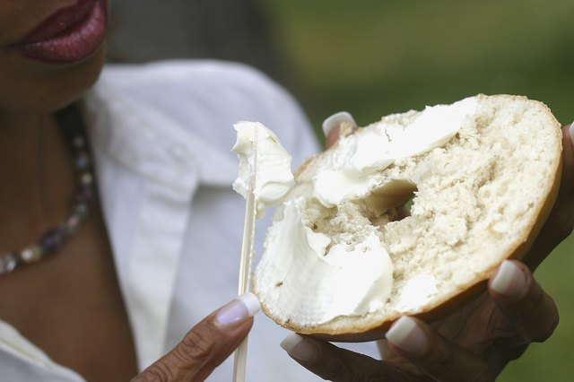 Close-up of a young woman holding a bagel