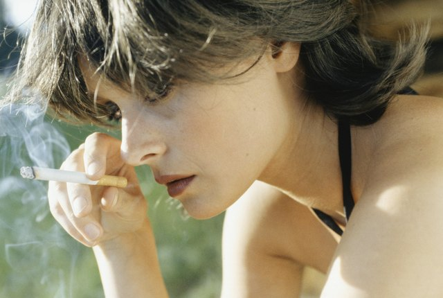 Young woman smoking cigarette, close-up