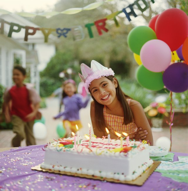 Girl (9-11) at birthday party, leaning over birthday cake, portrait