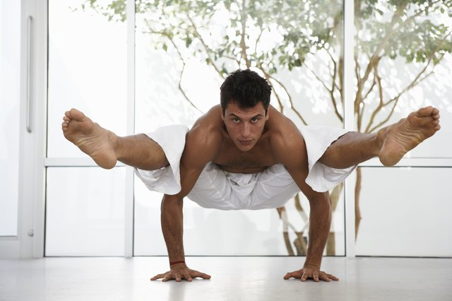 Man in yoga position balancing body off floor, portrait