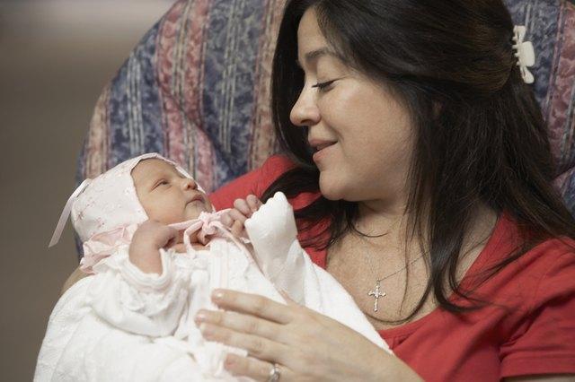 Hispanic mother smiling at newborn baby