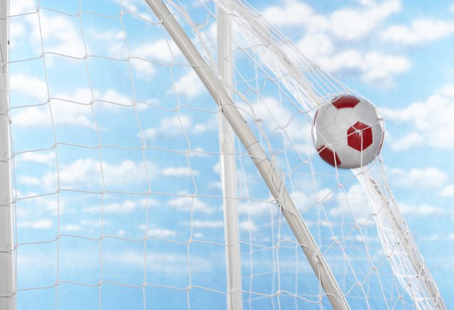 Soccer ball hitting back of net of goal