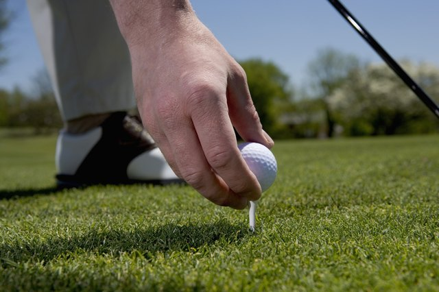 Close-up of a young man putting a golf ball on a tee