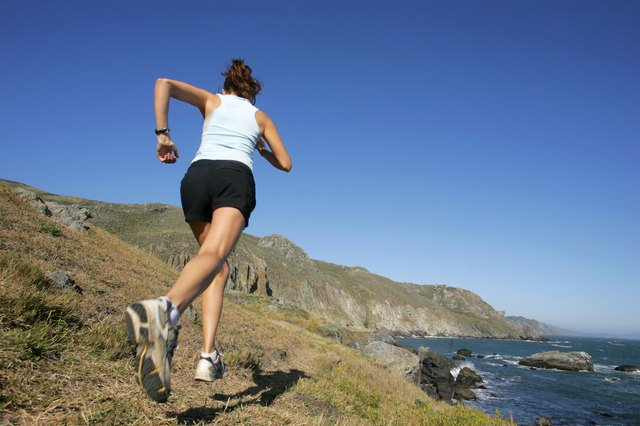 Woman running along coastline,  California,  USA