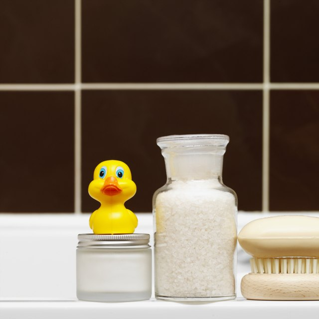 Close-up of toiletries and rubber duck on side of bath