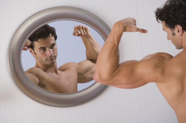 Muscular man looking in mirror and flexing arms
