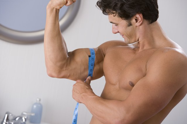 Muscular man measuring bicep