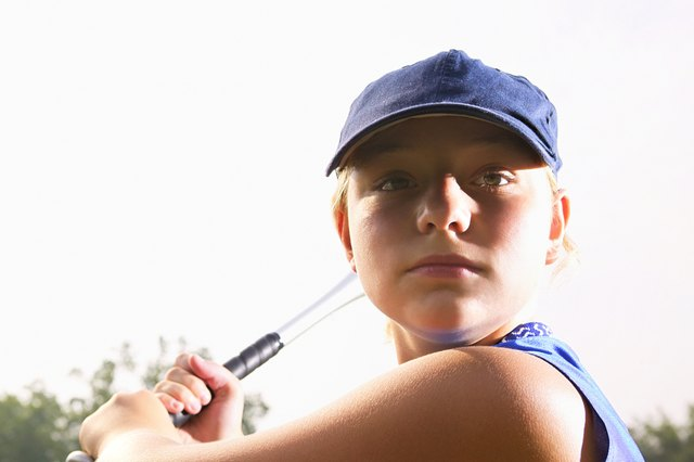 A softball player looking over her shoulder preparing to hit the ball