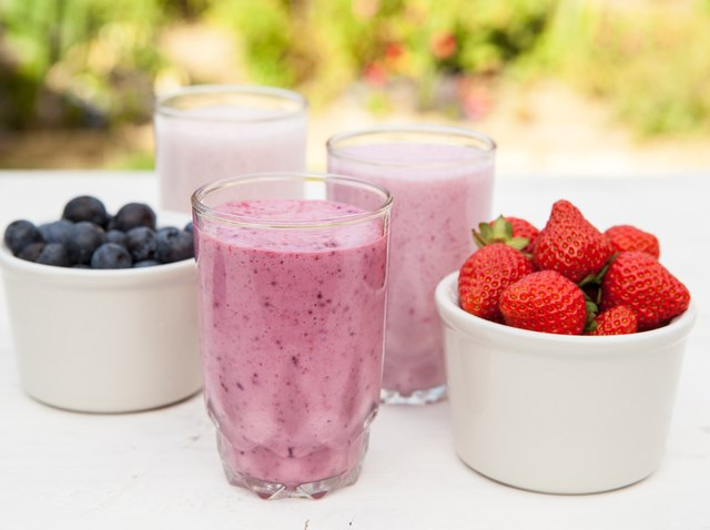 Three small glasses of smoothie on the white table