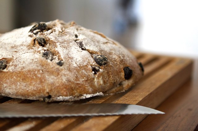 Loaf of sourdough bread with raisins on a wooden board