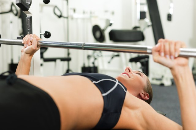 Woman in gym exercising with barbell