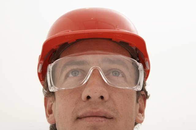 Man wearing protective eyewear and hard hat, looking up