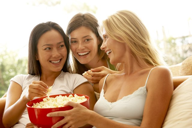 Friends eating bowl of popcorn