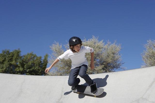 Teenage boy (16-17) skateboarding at skate park