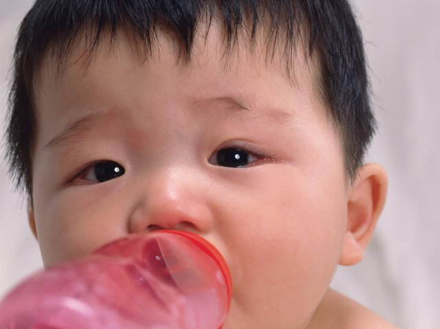 Close up of babys face, drinking milk, front view, portrait, Full Frame