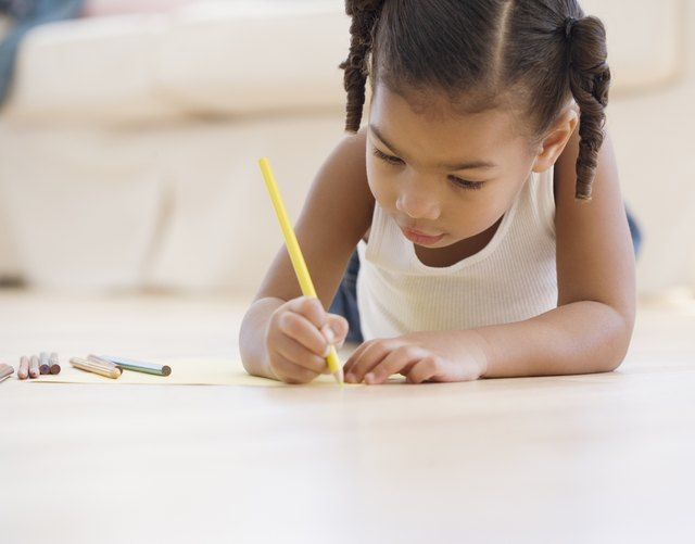 African girl coloring on floor