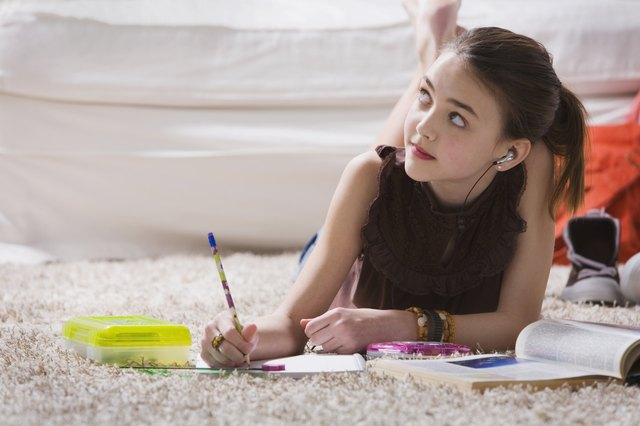 Young girl with headset doing homework on floor