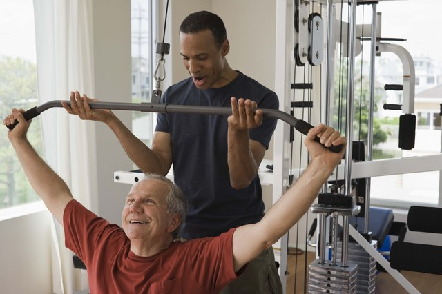 Personal trainer with man in home gym