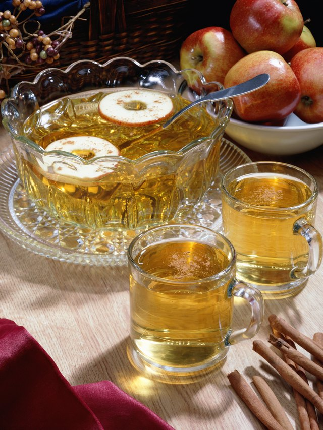 A bowl of apple cider with two glasses and a bowl of apples sitting on a table