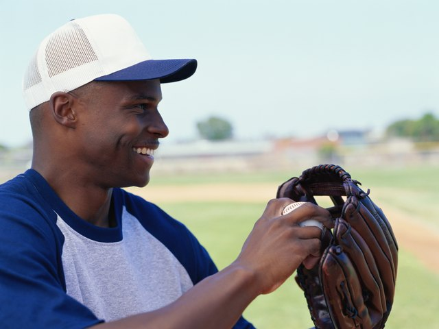 Baseball player holding baseball glove with ball, smiling, side view