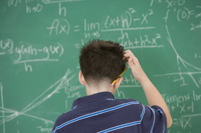 Hispanic boy scratching head in front of blackboard